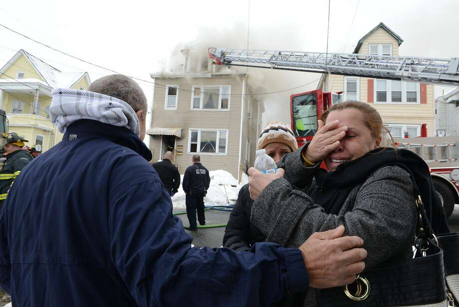 From left, Hector Gonzalez, a resident in the house, comforts his sister, Zoyla Gonzalez, who does not live in the house, as she reacts to the fire at a two-family home in Garfield, N.J., Tuesday, Feb. 18, 2014. (AP Photo/The Record of Bergen County, Tariq Zehawi) ONLINE OUT; MAGS OUT; TV OUT; INTERNET OUT;  NO ARCHIVING; MANDATORY CREDIT Photo: Tariq Zehawi, Associated Press