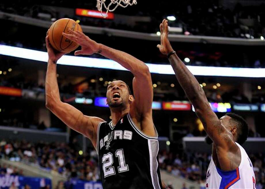 San Antonio Spurs forward Tim Duncan (21) gets by Los Angeles Clippers center DeAndre Jordan (6) for a basket in the first half of a NBA basketball game, Tuesday, Feb. 18, 2014, in Los Angeles.(AP Photo/Gus Ruelas) Photo: Gus Ruelas, AP / FR157633 AP