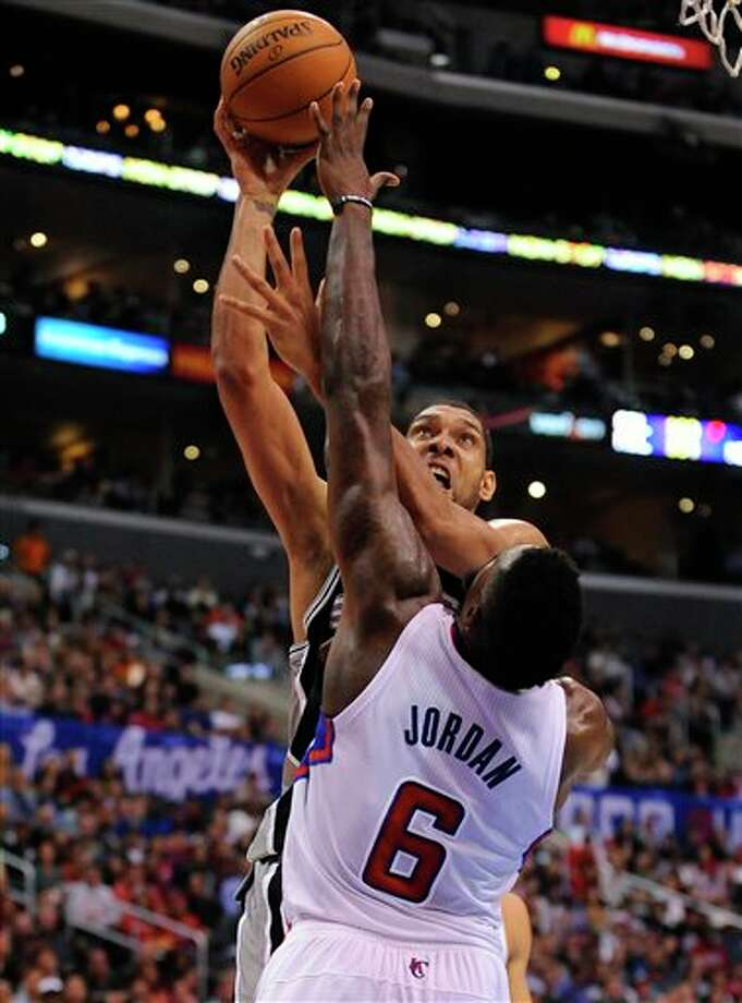 San Antonio Spurs forward Tim Duncan, back center, battles Los Angeles Clippers center DeAndre Jordan (6) as he makes a basket in the first half of a NBA basketball game, Tuesday, Feb. 18, 2014, in Los Angeles.(AP Photo/Gus Ruelas) Photo: Gus Ruelas, AP / FR157633 AP