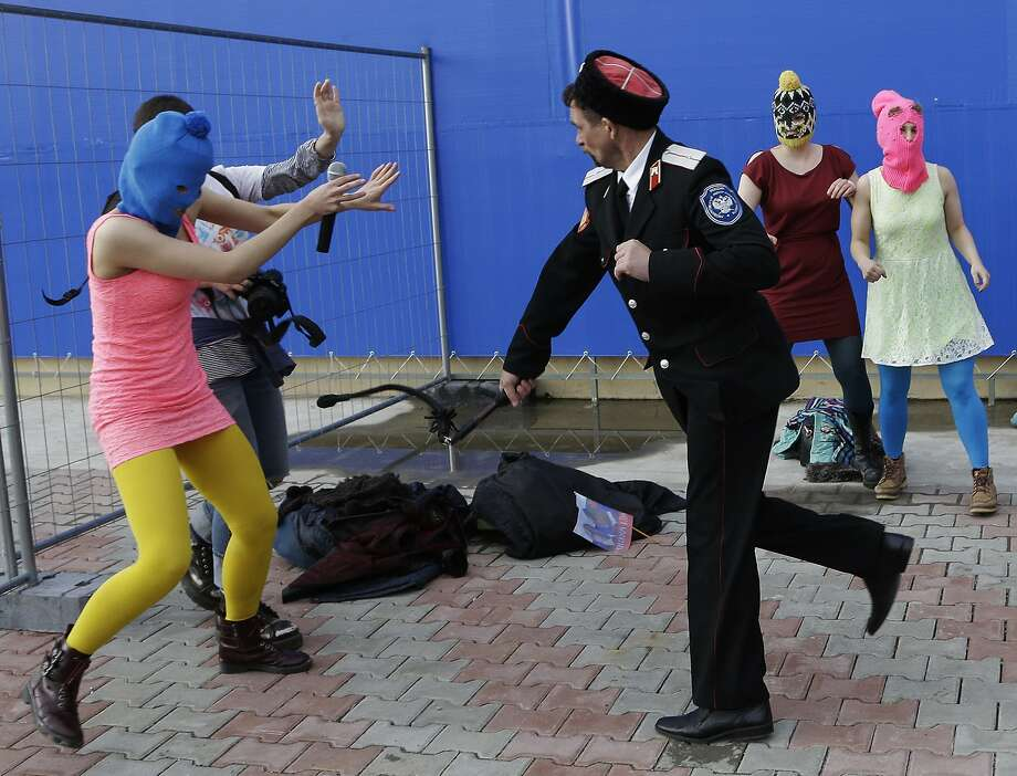 A Cossack militiaman attacks Nadezhda Tolokonnikova and a photographer as she and fellow members of the punk group Pussy Riot, including Maria Alekhina, right, in the pink balaclava, stage a protest performance in Sochi, Russia, on Wednesday, Feb. 19, 2014. The group had gathered in a downtown Sochi restaurant, about 30km (21miles) from where the Winter Olympics are being held. They ran out of the restaurant wearing brightly colored clothes and ski masks and were set upon by about a dozen Cossacks, who are used by police authorities in Russia to patrol the streets. (AP Photo/Morry Gash) Photo: Morry Gash, Associated Press
