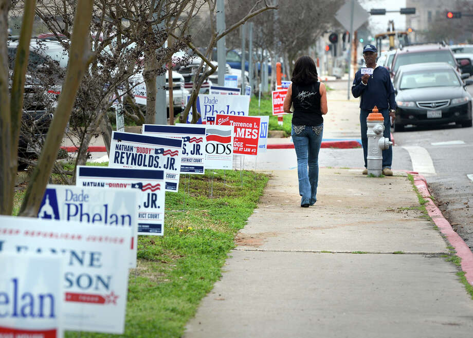 Earl Ricardo holds a political sign up as Reginal Mann walks toward him in front of the Jefferson County Courthouse on Tuesday. Early voting began a day late due to the President's Day holiday. Photo taken Tuesday, February 18, 2014 Guiseppe Barranco/@spotnewsshooter Photo: Guiseppe Barranco, Photo Editor