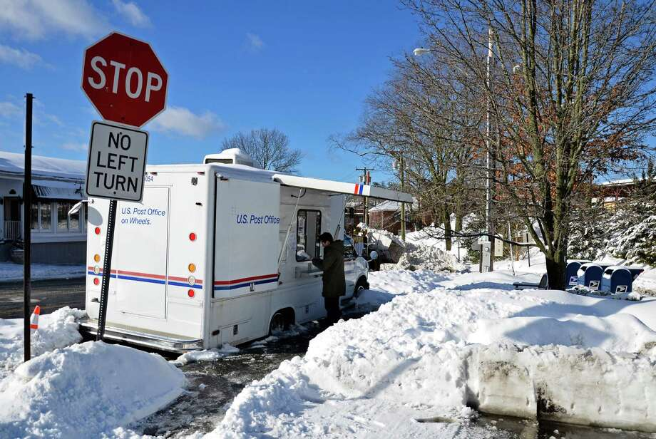 "A customer at the post office's mobile unit on Pine Street in New Canaan Friday morning, Feb. 14, 2014. Customers and town officials have said the truck is inconvenient, especially under inclement weather conditions, but U.S. Postal Service officials say the mobile unit is ""very temporary."" Photo: Nelson Oliveira / New Canaan News"