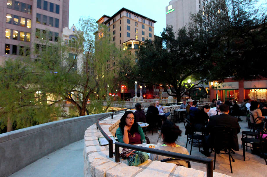 Dinner guests Teresa Ruiz (foreground) and her friend, Sylvia Galvan enjoy a mild evening on the patio at Lüke. Photo: KIN MAN HUI, Express-News / © 2012 San Antonio Express-News