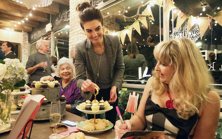 Bird Bakery owner Elizabeth Chambers (left) serves cupcakes as Teri Wilson signs copies of her new novel. Photo: Tom Reel / San Antonio Express-News