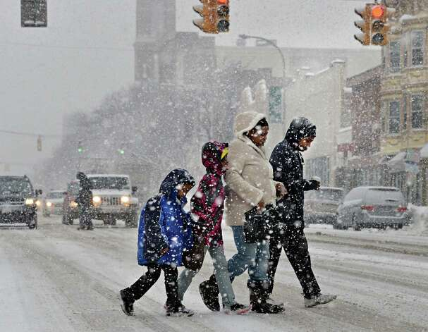 The Sheppard family of Albany: L'amir, 6, left, Lareina, 8, Tamyra and Jason, right, cross Central Avenue during a snow squall Wednesday, Feb. 19, 2014, in Albany, NY. (John Carl D'Annibale / Times Union) Photo: John Carl D'Annibale / 00025822A