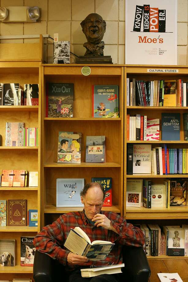 Ray Whelden peruses one of the thousands of books - four floors, new and used - at Moe's, beneath a bust of the store's late founder, Moe Moskowitz. Photo: James Tensuan, Special To The Chronicle