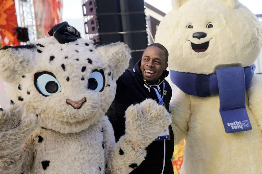 Jamaican bobsled brakeman Marvin Dixon poses with the Olympic mascots after a welcome ceremony at the Mountain Olympic Village prior to the 2014 Winter Olympics. Photo: Jae C. Hong, Associated Press