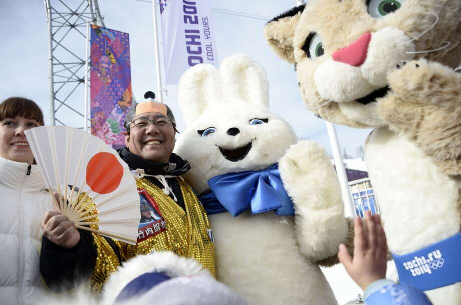 A Japanese fan poses with The Hare and The Leopard, two of the mascots of the 2014 Sochi Winter Olympics, as he attends the Men's and Women's Snowboard Parallel Giant Slalom qualification runs at the Rosa Khutor Extreme Park during the Sochi Winter Olympics on February 19, 2014. Photo: FRANCK FIFE, AFP/Getty Images