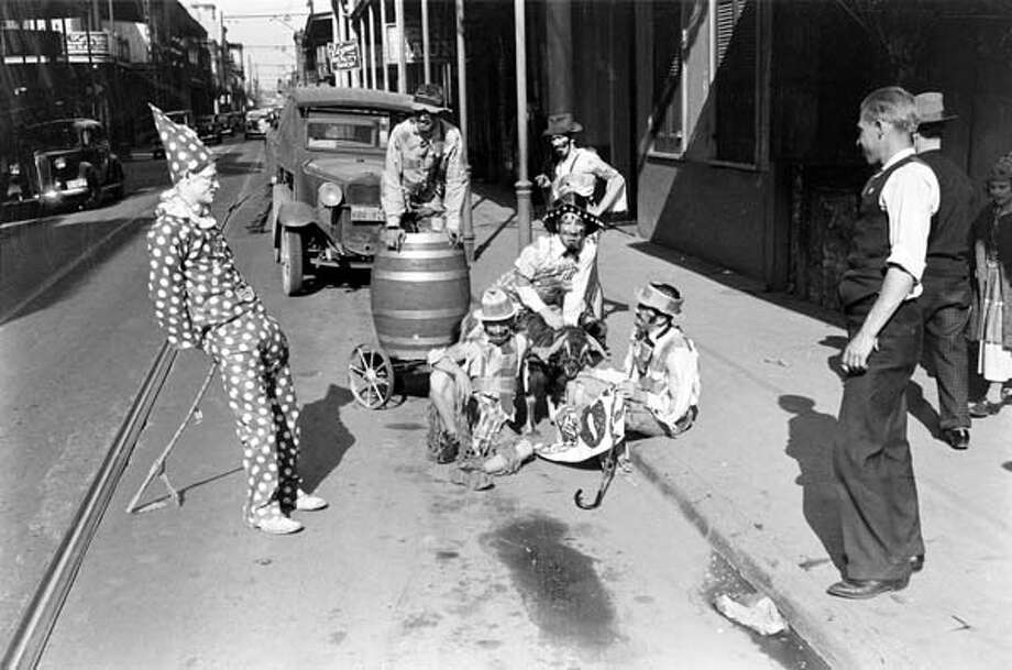 As several bystanders watch, a costumed group of people sit on the sidewalk and prepare for the Mardi Gras celebration in New Orleans, Louisiana in February 1938. Photo: William Vandivert, Time & Life Pictures/Getty Image / Time & Life Pictures