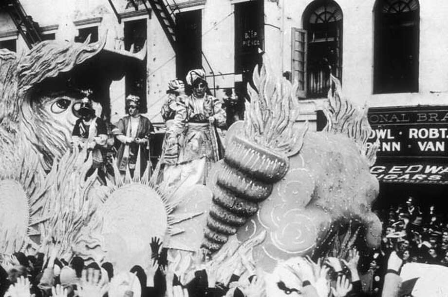 People in costumes give away prizes to the crowd while riding a float on a crowded street during a Mardi Gras parade in New Orleans, Louisiana circa 1945. The theme of the float is the elements: fire, wind, and sun are represented. Photo: Hulton Archive, Getty Images / Archive Photos