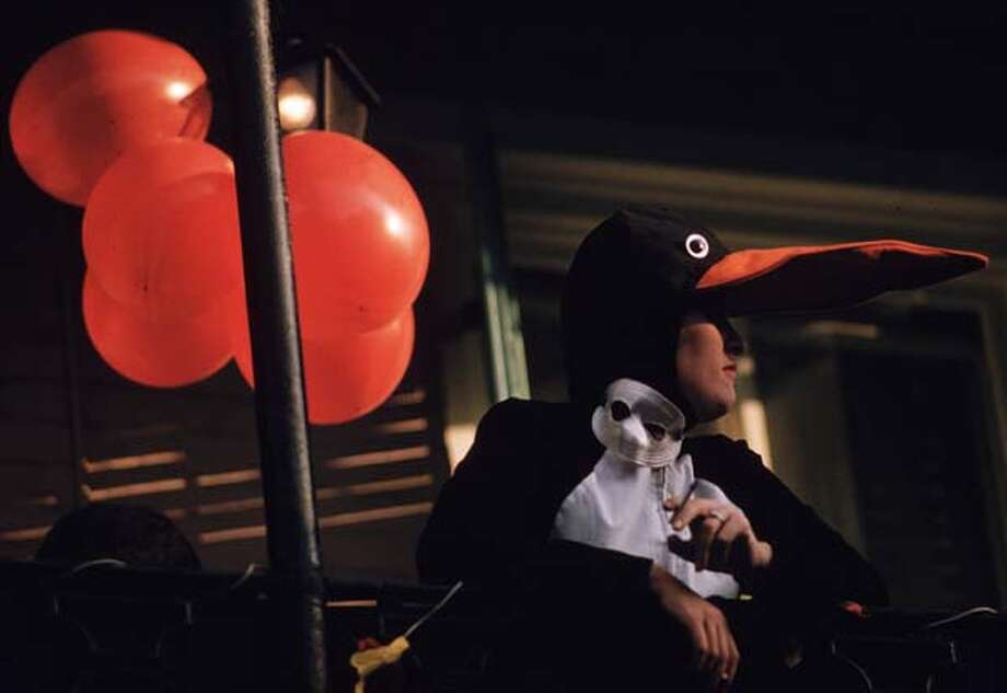 A woman in penguin costume during Mardi Gras in New Orleans enjoys a cigarette in February 1961. Photo: Ernst Haas, Getty Images / Ernst Haas