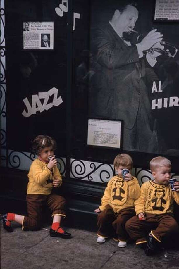Three children in identical yellow teddy bear tops drinking from paper cups during the Mardi Gras celebrations in New Orleans, Louisiana in February 1961. Behind them is a poster of jazz trumpeter Al Hirt. Photo: Ernst Haas, Getty Images / Ernst Haas