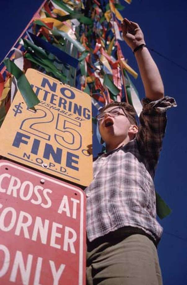 A Mardi Gras reveller in New Orleans, Louisiana stands by a decorated  street sign which forbids littering on pain of a $25 fine in February 1961. Photo: Ernst Haas, Getty Images / Ernst Haas