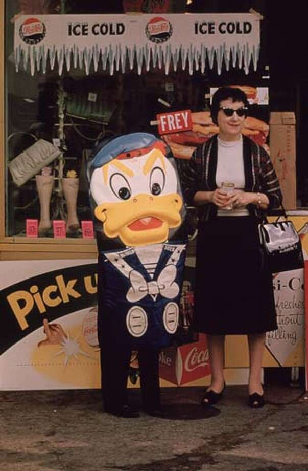 A woman and somebody dressed as Donald Duck by a Pepsi-Cola stand during Mardi Gras in New Orleans, Louisiana in 1961. Photo: Ernst Haas, Getty Images / Ernst Haas