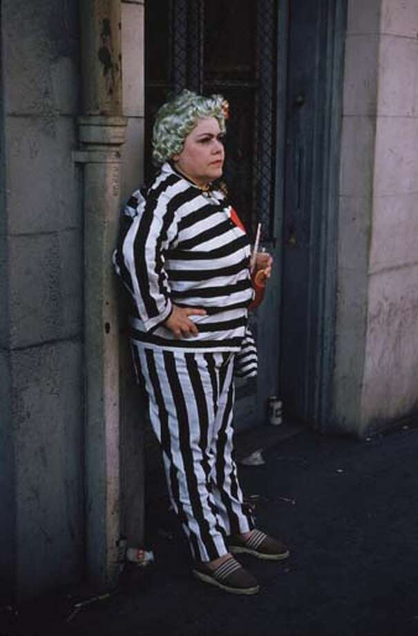 A woman in a black and white striped suit and a green wig watches the Mardi Gras celebrations in New Orleans in February 1961. Photo: Ernst Haas, Getty Images / Ernst Haas