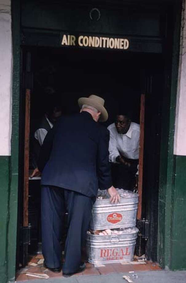 Cans of beer packed in ice are being inspected in a doorway during Mardi Gras in New Orleans, Louisiana in February 1961. Photo: Ernst Haas, Getty Images / Ernst Haas