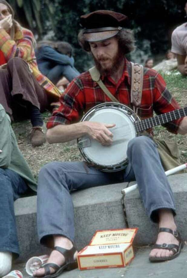 An unidentified man sits on a curb with an open cigar box at his feet as he plays a banjo for money during the Mardi Gras parade in New Orleans, Louisiana in February 1973. Photo: Tim Boxer, Getty Images / Archive Photos
