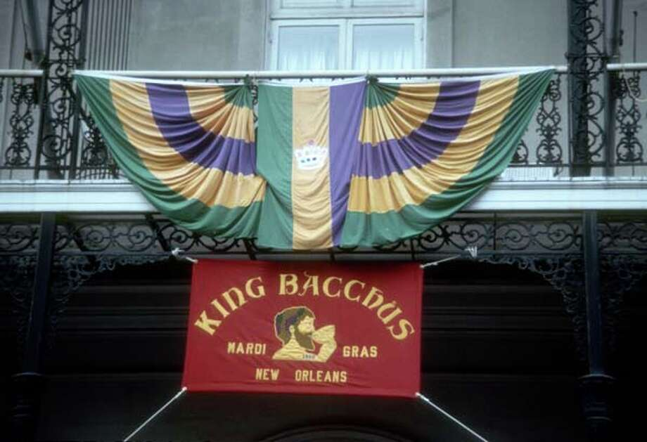 View of green, yellow, and purple bunting, along with a sign for 'King Bacchus,' hang from a balcony during the Mardi Gras parade in New Orleans, Louisiana in February 1973. Photo: Tim Boxer, Getty Images / Archive Photos