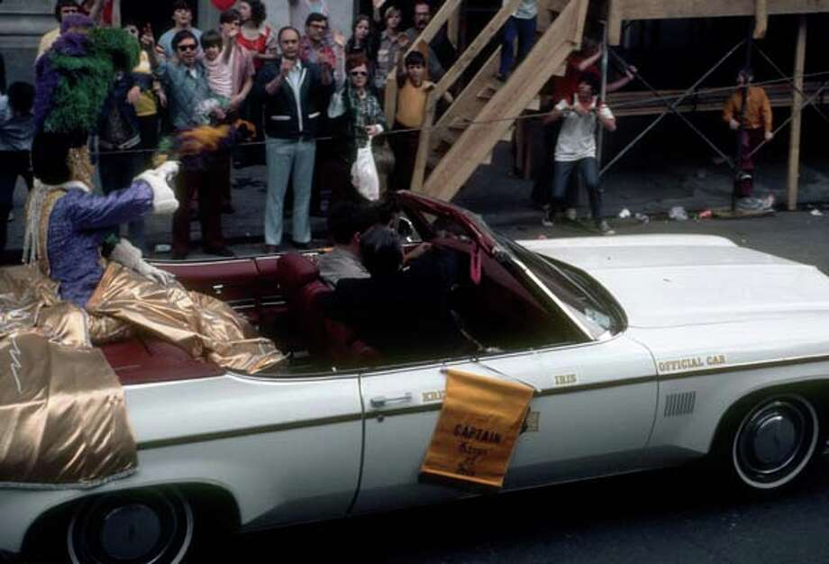 View of a costumed participant who waves from an open-top 'official car' during the Mardi Gras parade in New Orleans, Louisiana in February 1973. Photo: Tim Boxer, Getty Images / Archive Photos