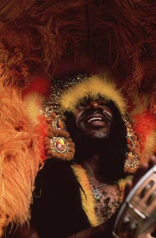 A man wears a magnificent feathered headdress in orange and yellow and plays a tambourine for Mardi Gras in New Orleans, Louisiana in 1979. Photo: Ernst Haas, Getty Images / Ernst Haas
