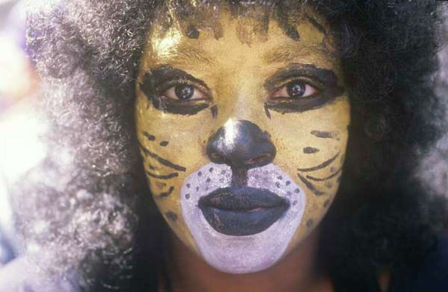 A woman celebrates Mardi Gras while wearing cat makeup in New Orleans, Louisiana in January 1988. Photo: Visions Of America, UIG Via Getty Images / © 2004 VisionsofAmerica.com/Joe Sohm.  All Rights Reserved. (800) SOHM-USA (764-6872)