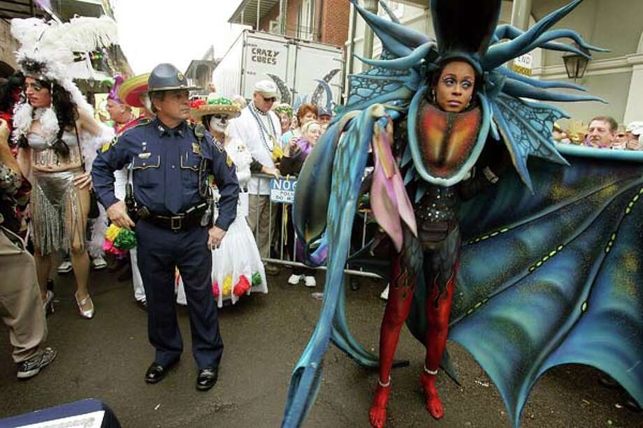 A police officer looks at a contestant waiting to go onstage in the Bourbon Street Awards for costume design during Mardi Gras festivities on February 8, 2005 in New Orleans, Louisiana. Photo: Mario Tama, Getty Images / 2005 Getty Images
