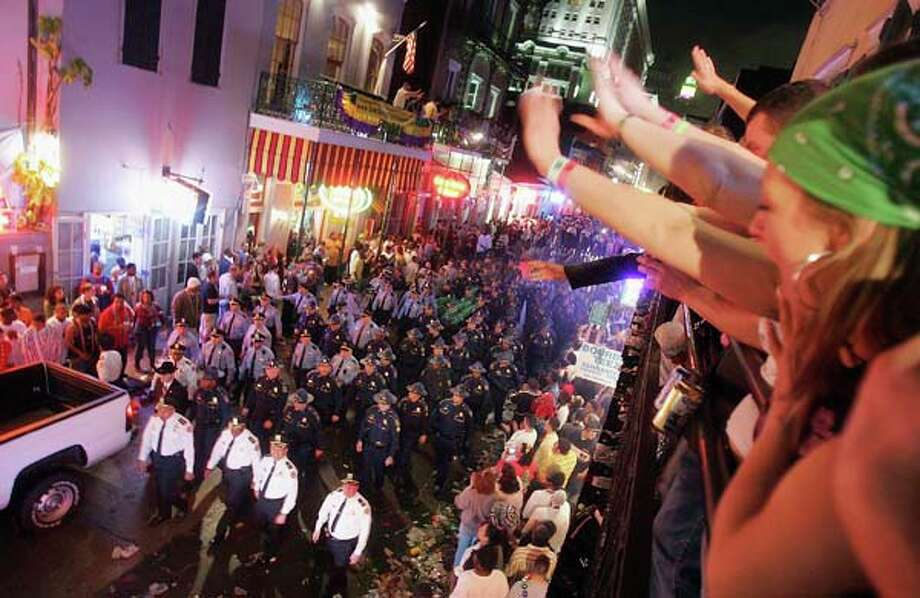 Revelers watch as police officers clear Bourbon Street at midnight at the official conclusion of Mardi Gras festivities on February 9, 2005 in New Orleans, Louisiana. Photo: Mario Tama, Getty Images / 2005 Getty Images