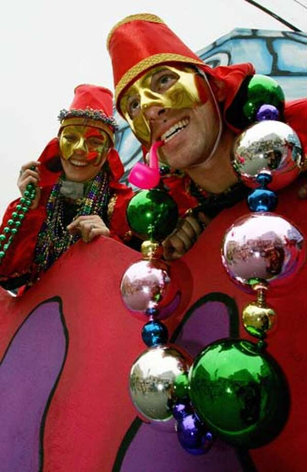 Jeremy Herschaft (R) and his wife Niki throw beads from a float during the Pontchartrain parade opening at the Mardi Gras celebrations in New Orleans on February 18, 2006. Photo: ROBYN BECK, AFP/Getty Images / 2006 AFP