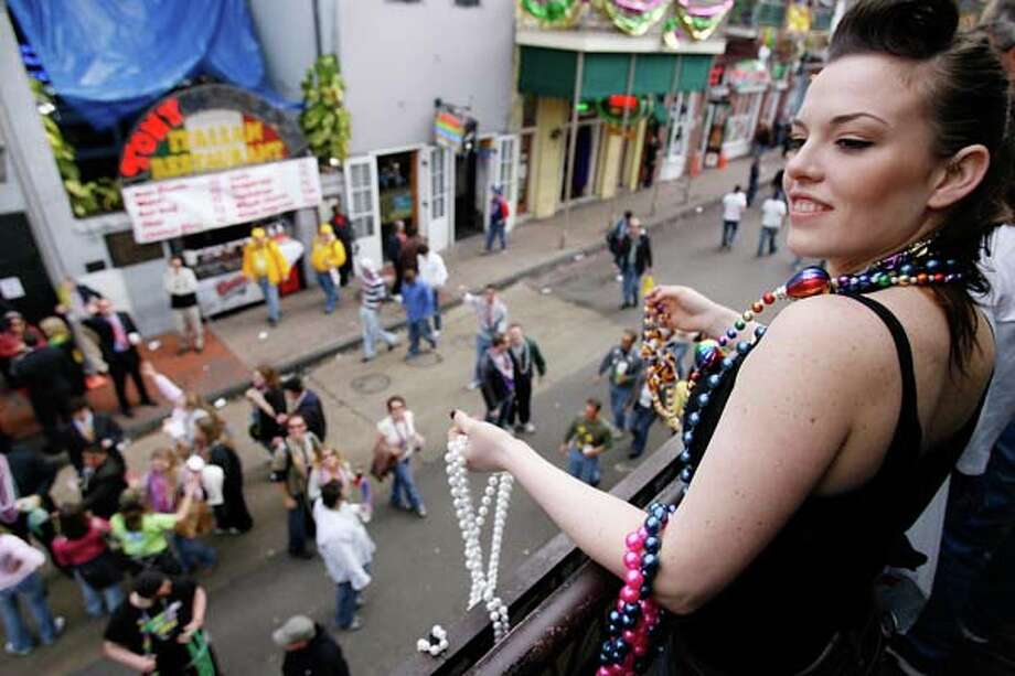 A woman looks to throw a pair of beads from a balcony on Bourbon Street on Lundi Gras (the Monday before Mardi Gras) on February 19, 2006 in New Orleans, Louisiana. Photo: Chris Graythen, Getty Images / 2007 Getty Images