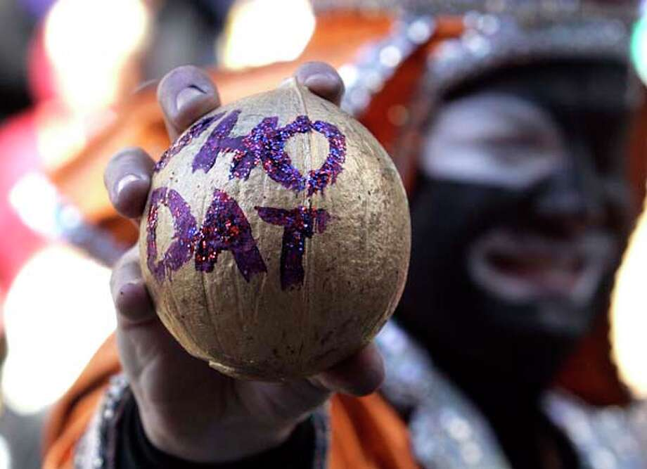 "A member of the Zulu Social Aid and Pleasure Club displays a gold coconut with the words ""who dat"" during Mardi Gras Day on February 16, 2010 in New Orleans, Louisiana. Photo: Pat Semansky, Getty Images / 2008 Getty Images"