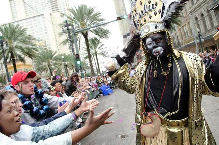 A member of the Krewe of Zulu taunts the crowd with the club's signature throw, a decorated coconut, as the Krewe of Zulu turns onto Canal Street from St. Charles Avenue during the Mardi Gras parade on Fat Tuesday in New Orleans, Louisiana on March 8, 2011. Photo: AFP, AFP/Getty Images / 2011 AFP
