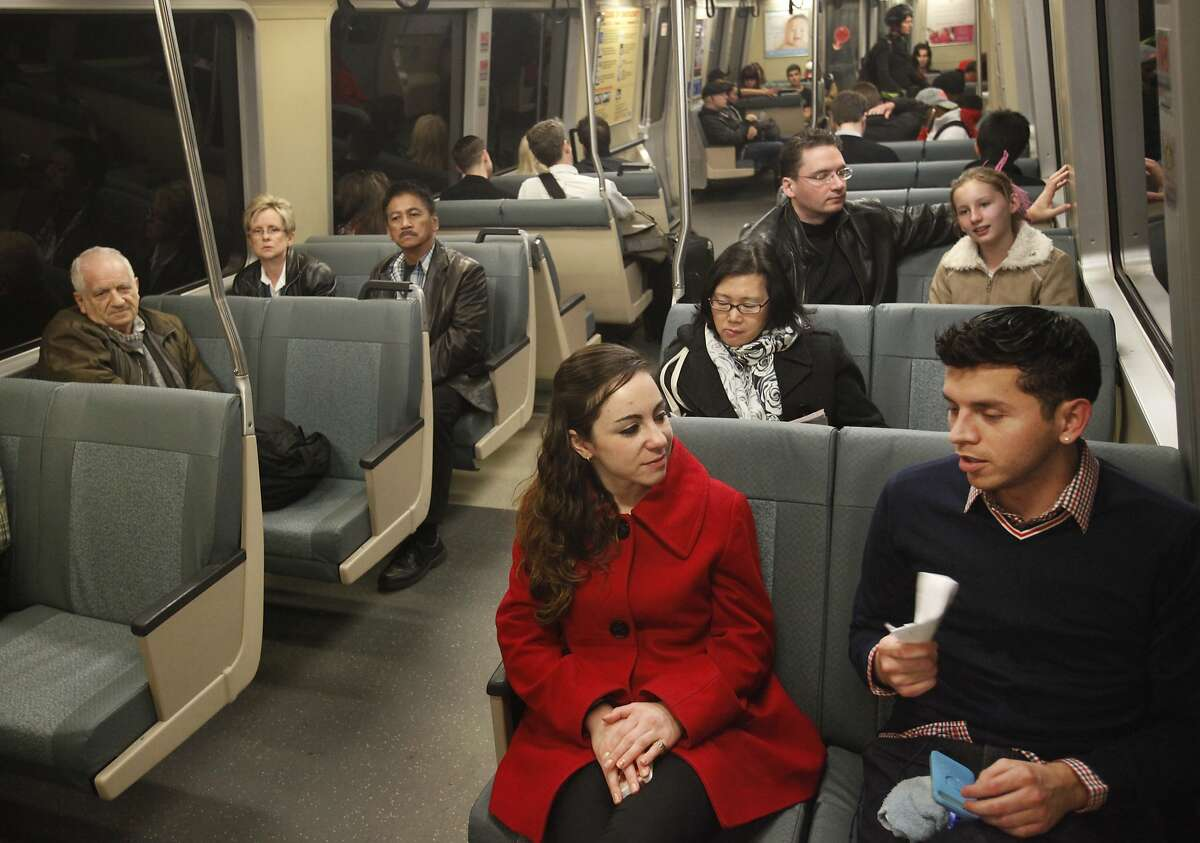 Sarah Musiker, 24, left, chats with David Lopez, 26, right, as he fans himself because of warm temperatures in the car Feb. 14, 2014 as they ride a BART train to San Francisco going through Oakland, Calif. Some people have complained that some BART cars are too hot.