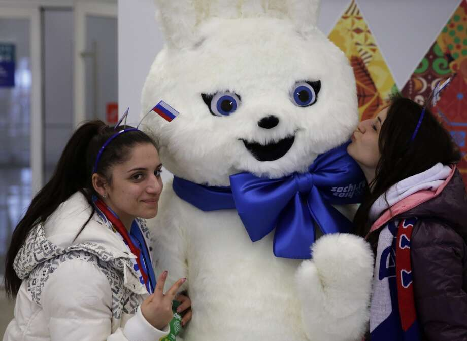 Girls pose for a photograph with a mascot of the 2014 Winter Olympics prior to the start of the men's 500-meter speedskating race at the Adler Arena Skating Center in Sochi, Russia, Monday, Feb. 10, 2014. Photo: Matt Dunham, Associated Press