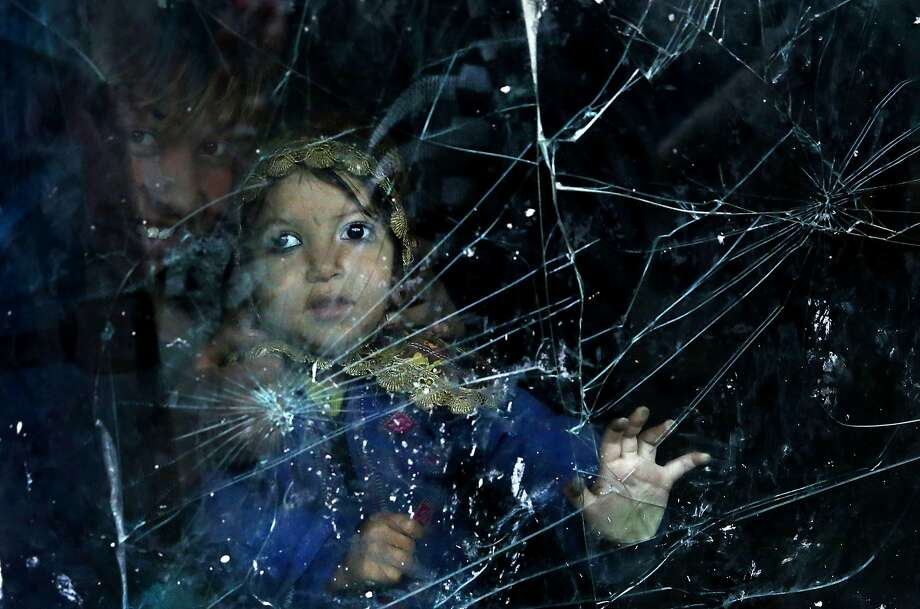 An Afghan internally displaced girl looks through a window made of a broken car windshield at their home in a poor neighborhood in Kabul, Afghanistan, Wednesday, Feb. 19, 2014. (AP Photo/Massoud Hossaini) Photo: Massoud Hossaini, Associated Press