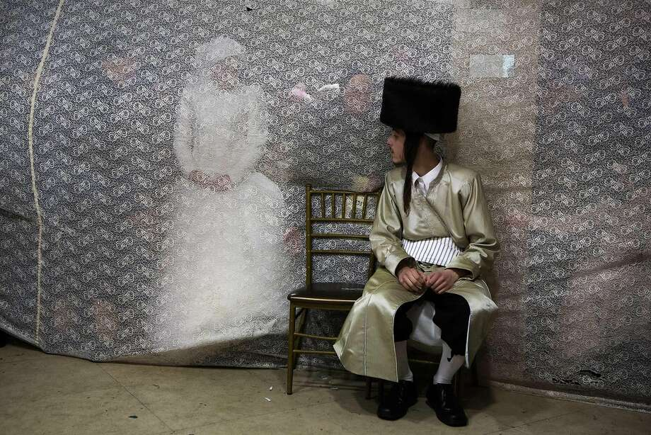 An ultra-orthodox dance card: Aharon Krois looks at his bride, Rivka Hannah (Hofman), through a curtain during the Mitzvah Tans dance ritual following their wedding in Jerusalem. The ritual calls for the bride to dance with members of the community, family and the groom. Photo: Menahem Kahana, AFP/Getty Images