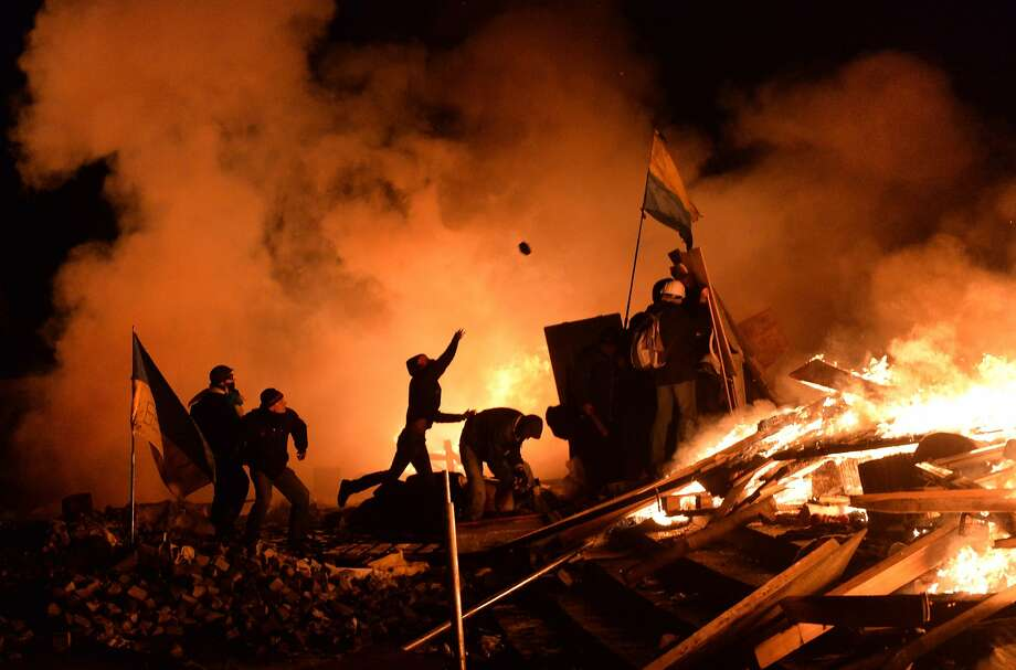 Kiev crisis ratchets up:Behind burning barricades, anti-government protesters throw cobblestones at police in Kiev's 