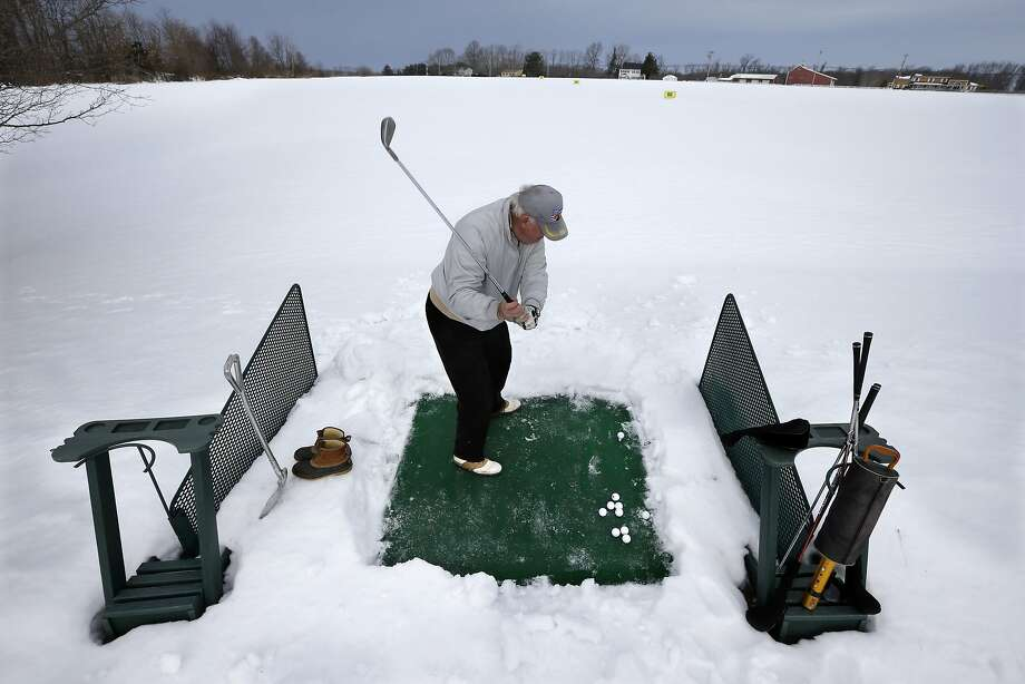 Where they land nobody knows: Never one to let winter interfere with his golf, Rich Lukasik works on his drive in Cream Ridge, N.J. Photo: Mel Evans, Associated Press