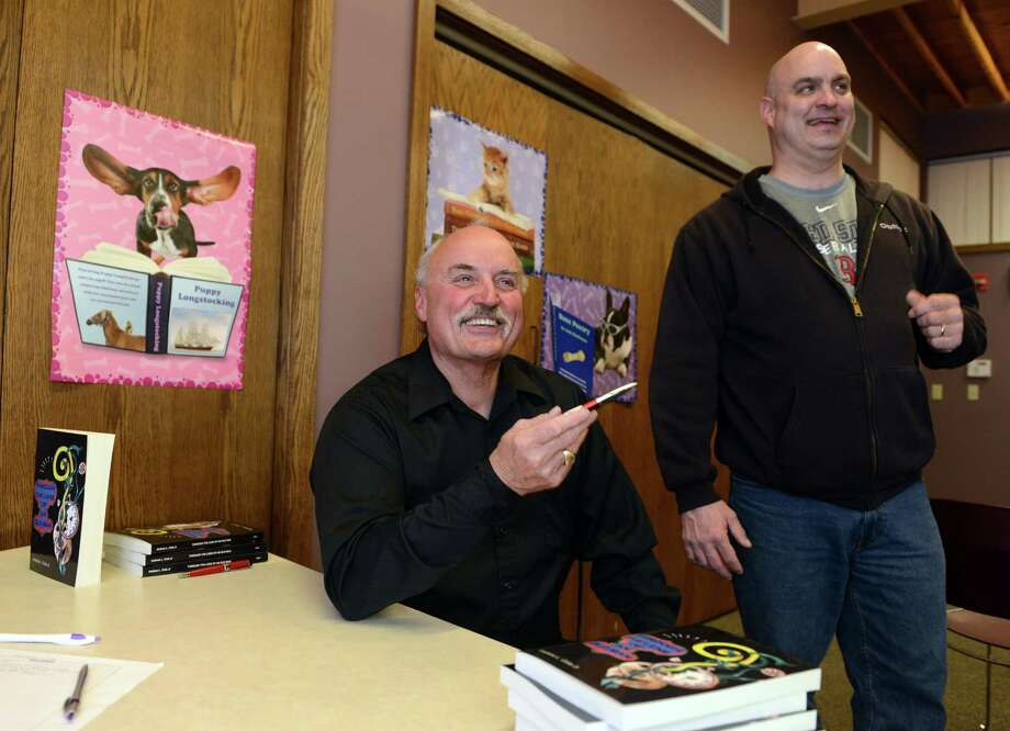 """Retired Derby Police Chief Andrew L. Cota Jr. and his son Ansonia Police Lt. Andrew L. Cota III chat following a discussion of his father's new book """"Through The Lens of An Old Man"""" Tuesday, Feb. 18, 2014, at Derby Neck Library. Photo: Autumn Driscoll / Connecticut Post"""