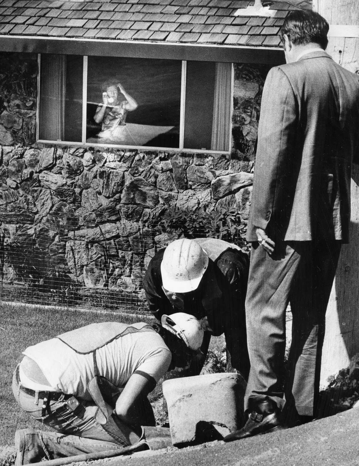 Above: Phyllis Olson watches as an EBMUD crew installs a water restrictor to limit flow from 883 gallons per month to 225.
