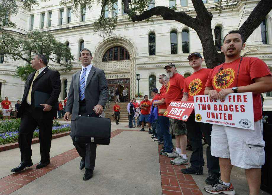 Councilman Ron Nirenberg walks by police and firefighters union members gathered in force as City Council prepares to hear the recommendations of a task force considering their retirement and health benefits on Wednesday, Feb. 19, 2014. Photo: Billy Calzada, San Antonio Express-News / San Antonio Express-News