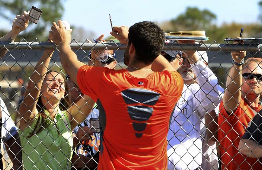 J.D. Martinez signs autographs for fans over the fence after workouts. Photo: Karen Warren, Houston Chronicle