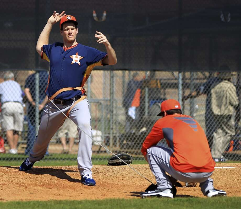Bobby Doran, standing, and Nick Tropeano, kneeling, test out a system of ropes and bungees intended to help pitchers during workouts. Photo: Karen Warren, Houston Chronicle