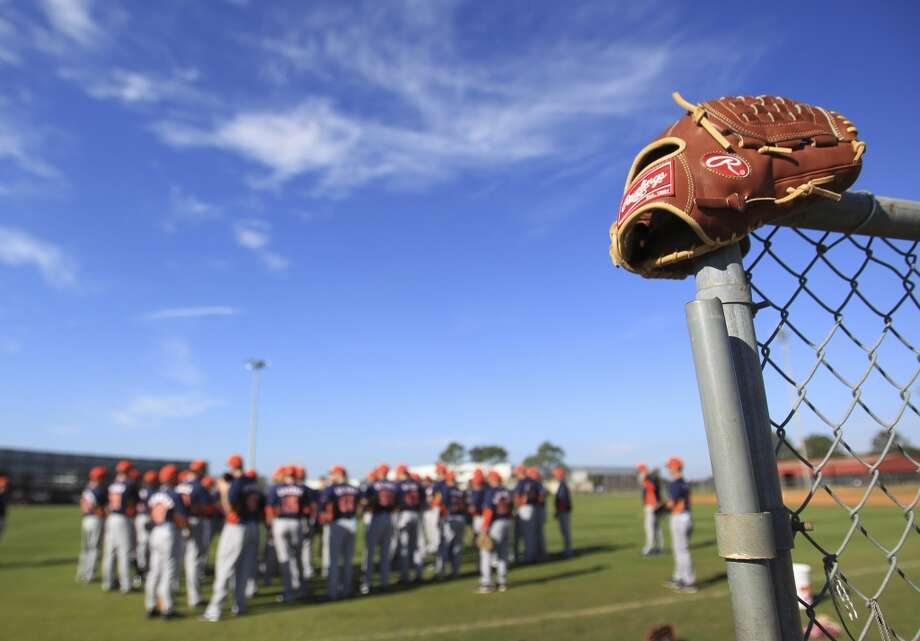 A glove sits atop a fence as players stretch before workouts. Photo: Karen Warren, Houston Chronicle
