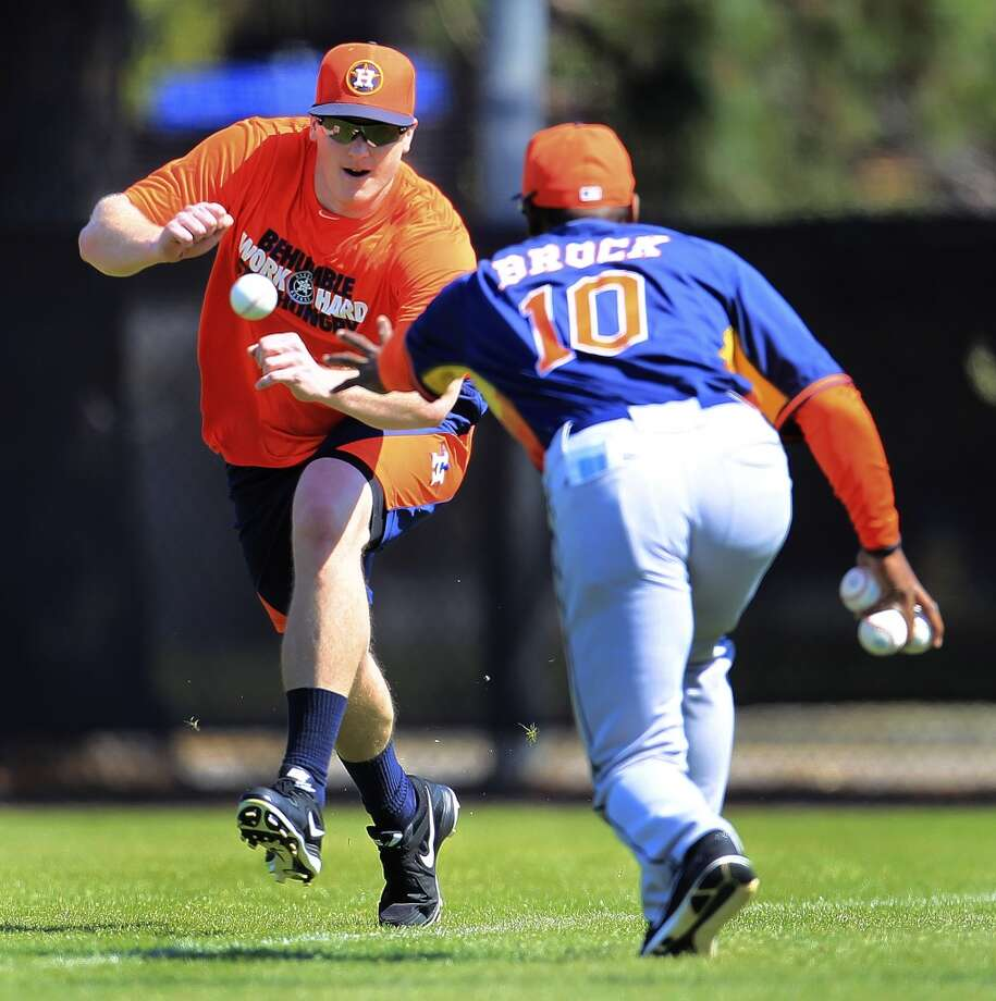 Astros first base coach Tarrik Brock runs a drill with outfielder Marc Krauss during workouts. Photo: Karen Warren, Houston Chronicle