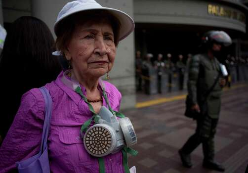 Arminda Alvarado, 85, supporter of opposition leader Leopoldo Lopez stands outside the Palace of Justice to show her solidarity with him, in Caracas, Venezuela, Wednesday, Feb. 19, 2014. Following a dramatic surrender and a night in jail, Venezuelan opposition leader Leopoldo Lopez was due in court Wednesday to learn what charges he may face for allegedly provoking violence during protests against the socialist government in the divided nation. Photo: Rodrigo Abd, AP / AP