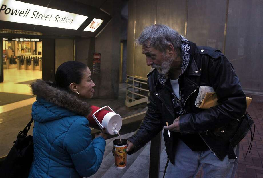 Oli Medin, who is among the people rallying to help Steve Goff, brings him hot chocolate. Photo: Lacy Atkins, The Chronicle