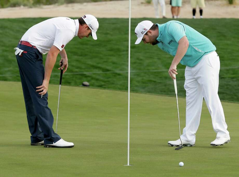 Jimmy Walker, right, and Branden Grace, of South Africa, look over their putts on the second hole during the first round of the Match Play Championship golf tournament on Wednesday, Feb. 19, 2014, in Marana, Ariz. (AP Photo/Ted S. Warren) Photo: Ted S. Warren, Associated Press / AP