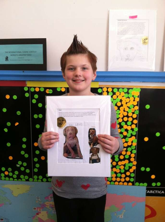 Forest Park Elementary School fourth-grader Emma VanPatten shows off her winning entry in the ?World?s Greatest Dog: An international Canine Contest.? organized by the International Center of the Capital Region and World Awareness Children?s Museum. Area elementary school students were asked to explain why their dog is the greatest through a drawing and a written description. About 100 entries were submitted and are on exhibit at the Children?s Museum at 89 Warren St. in Glens Falls. Later this year, the 12 winning entries will be in a traveling exhibit.