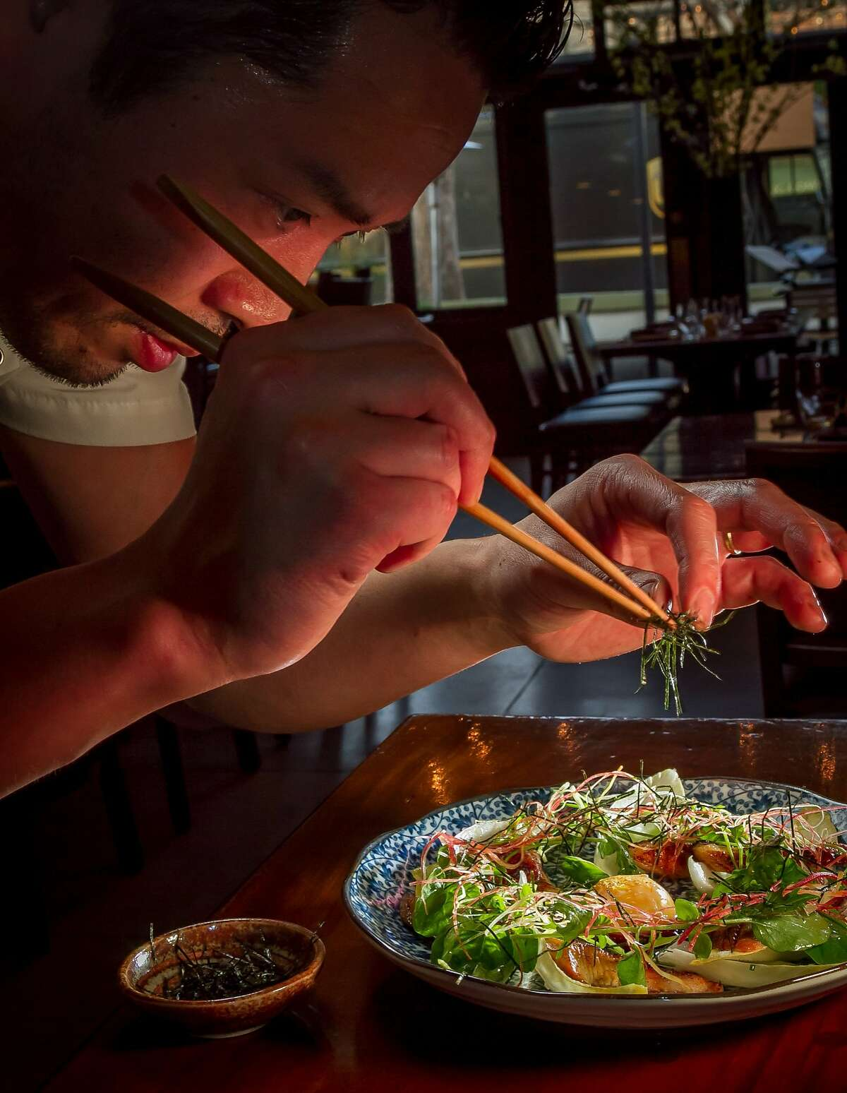 Chef Sho Kamio adds the final touches to the Unagi Saad at Iyasare restaurant in Berkeley, Calif., is seen on Monday, February 10th, 2014.