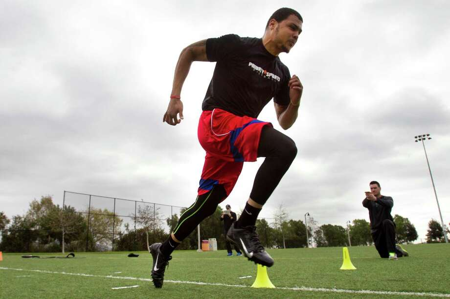 Receiver Mike Evans, who is intent on breaking 4.5 in the 40 at the NFL combine, is timed by speed coach Ryan Flaherty while training in Carlsbad, Calif. Photo: Brett Coomer, Staff / © 2014 Houston Chronicle